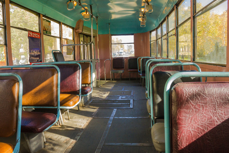 eldest: The inner part of the old tram, all the places are free, there is no one. Sunny autumn day, urban conditions.