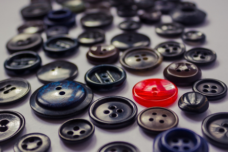 soltería: Among the buttons of dark color, a red one stands out. Violation of general rules, dress code, personality among the crowd. Side view, natural lighting. Foto de archivo