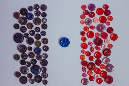 Buttons for clothes of red and dark shades. In the middle of a striped blue button. Sewing accessories, products for making clothes. View from above. Stock Photo