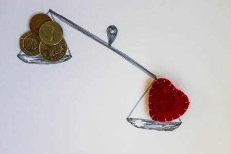 On the scales of the coin and the red heart. Sincere feelings are more important. White background, top view. Stock Photo