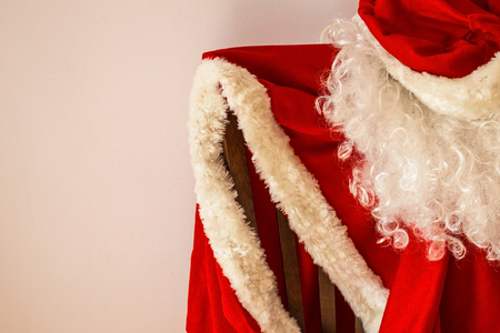 The red outfit of Santa Claus hangs on a chair. Approaching the holiday, the New Year, the fulfillment of desires.