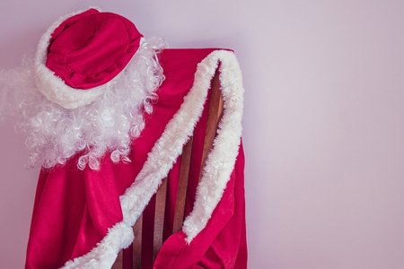 The red suit of Santa Claus is waiting on the chair of the beginning of the holiday. Soon the New Year, there are last preparations. Daylight, lilac tint.