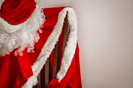Santas outfit hangs on a chair. Help yourself, take a step towards your dream. Give your loved ones a New Years fairy tale. Daylight. Stock Photo