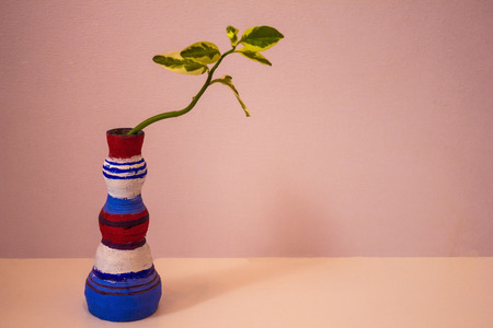 A colored earthenware vase, a childrens hand-crafted article for my mother. Congratulations on the holiday, Happy Birthday. In the vase is a green sprout. Daylight.