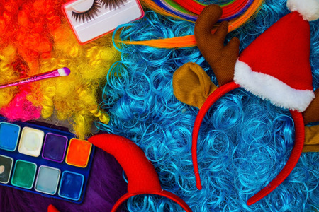 Bright colored wigs, makeup, false eyelashes. Preparation for the New Years party. Daylight.
