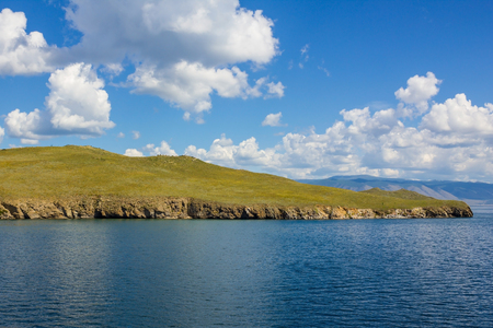 Part of a small island stands at sea. Beautiful, bright landscape. The blue sky with cumulus clouds is reflected in the water. Olkhon Island on Lake Baikal. Stock Photo