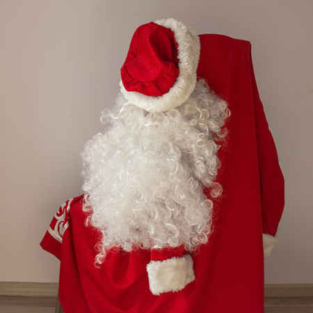 Santas bright red suit is hanging on a chair. Soon the holiday is New Year, its time to prepare for the celebration.