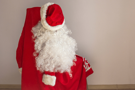 The outfit of Santa Claus hangs on a chair. Soon the New Year, everyone can become Santa. Daylight. Stock Photo