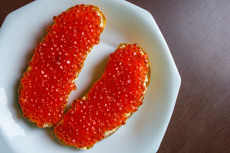 sumptuousness: Two sandwiches with red caviar on a white plate. Brown table, daytime side lighting. View from above. Stock Photo