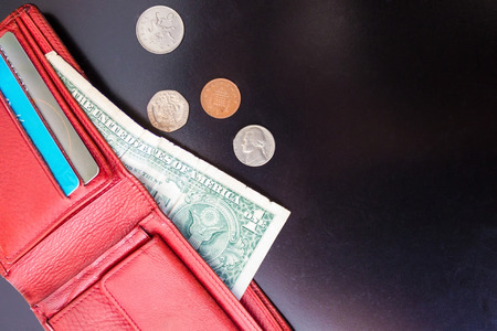 From the purse sticks out one dollar and credit cards, next to it lie a few small coins. Dark background, top view.