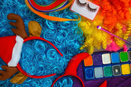Against the background of blue, purple and yellow hair, there is a colored make-up, a make-up brush, false eyelashes and New Years accessories.