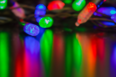 Festive garland with colored light bulbs. Lanterns are reflected by vertical stripes on a dark surface. The background is blurred. Stock Photo