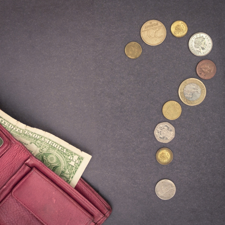 Question mark from coins. Financial problems, unforeseen expenses. Shortage of cash. Gray background.