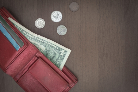 A purse and small money, cash. Money problems, despair, impoverishment, a small salary. Vignetting, top view.