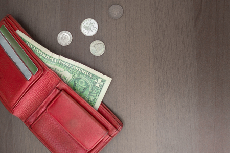 On the brown surface is a red purse with a dollar and credit cards, alongside small coins. Cash settlement, the price of the issue, lack of money.