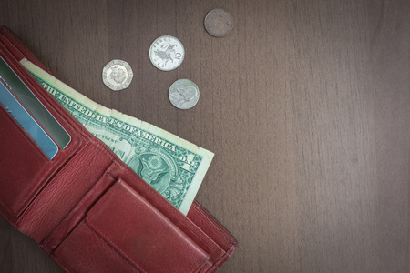 From the purse sticks out one dollar, next to small coins. Lack of money, low salary. Muted tone, vignetting.