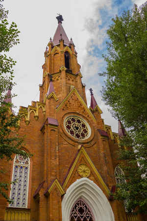 The church in the modern city, the Romanesque style. Facade, view from below. Its a nasty day. Partly cloudy. Stock Photo