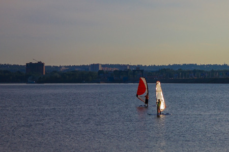 Windsurfing on an urban pond. A guy and a girl in the middle of a water surface under sails. Active, youth vacation. Imagens