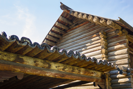 An old wooden building made of round wood, handmade, carpentry. Covering the roof with hollow logs. Ancient wooden architecture. Stok Fotoğraf