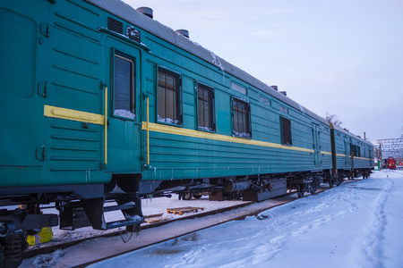 Green freight cars are on the rails. Cargo transportation services. Winter, around the snow.