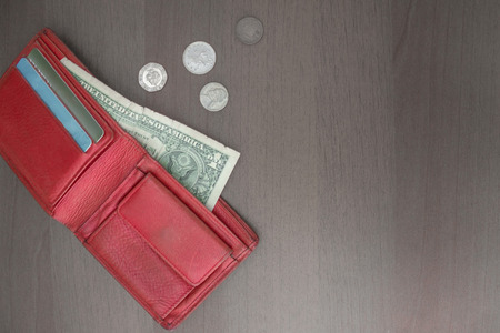 A red wallet with a dollar and credit cards, next to several coins. Hopelessness, a difficult financial situation, devotion, low incomes. Stock Photo