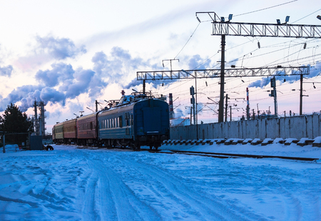 The last cars of the train leave the station. Late, miss your chance. Winter, snow around, cold evening, twilight.