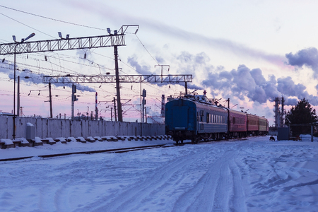 Railway station, the composition goes away, the last cars of the train are visible. Around the snow, a cold winter evening.