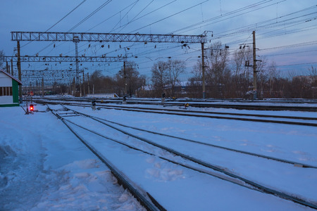 Railway station, platform. The rails are covered with snow. Several options for directions, ways. Winter evening, dusk.