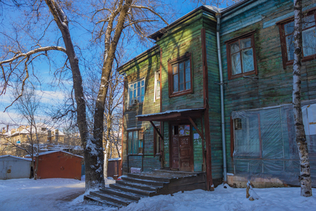 Old wooden house, dilapidated building. In the yard there is snow, in the background there are iron garages. City line. Stock Photo