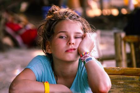 Een Europees uitziend meisje met een gezicht dat verveling en anticipatie uitdrukt. Aziatisch café, reizen met kinderen, lokale keuken. De achtergrond is wazig. Stockfoto