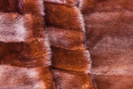 Rich fur garment, luxury. A brown mink with a dense, long nap, a womans fur coat, a mantle. Winter outerwear. Stock Photo