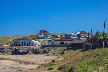 A small village on the island, an abandoned port, rusty ships on the shore. Far away on the hillock is an Orthodox church, a wooden building. The blue sky, clear day.
