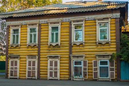 A two-storey yellow dwelling house made of wood, a city street. On the windows are shutters, carved platbands. Wooden architecture, handmade. Stock Photo