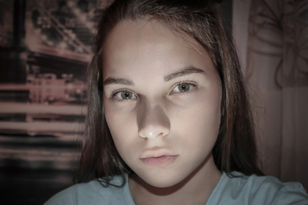 Portrait of a girl with frightened eyes. Childrens fears, anxieties, nightmares. Difficulties of adolescent psychology. Evening, room, artificial lighting from below. Stock Photo