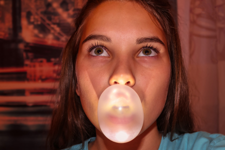 Portrait of a modern schoolgirl, a teenager puffing a bubble of chewing gum. The view is directed upwards. Problems of growing up, the age of transition, child psychology.