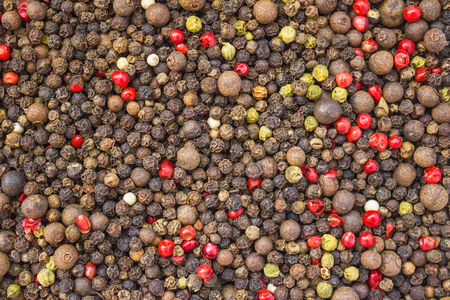 Background of red, black, white and green dried peppercorn. Spicy seasoning, piquancy, fragrant spice. Cooking, culinary secrets.