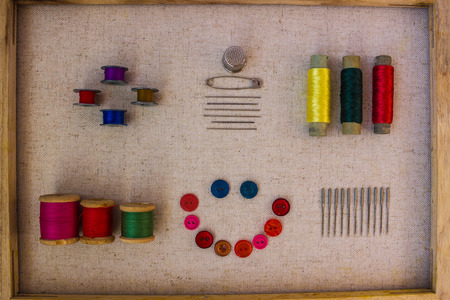 Coils with threads, colored bobbins, needles and buttons for clothes on a light background of matting. Along the perimeter there is a wooden frame. View from above.