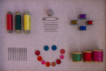 In the center is a funny face made of buttons, around sewing accessories. Top view, lilac toning. Daylight.