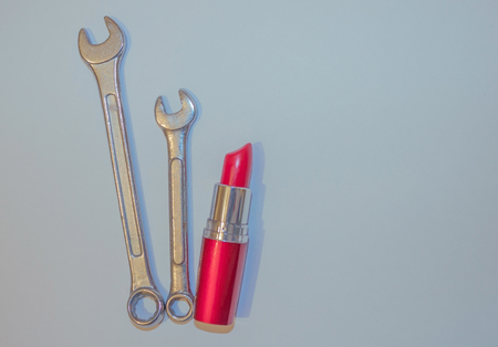 Wrenches and scarlet lipstick. Strong, independent woman, leader. Femininity and firmness. Blue toning, top view.