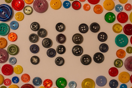 Boredom among the general fun, life in black, negative mood, depression. Bright background of colored buttons for clothes, in the middle the inscription is