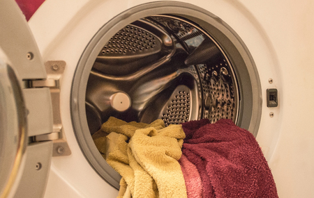 In the drum of the washing machine there are several terry towels. Laundry, household care. Artificial lighting.