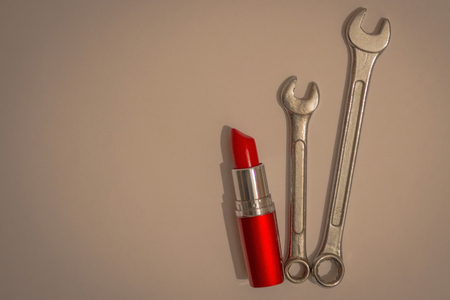 Bright red lipstick and two metal spanners. An independent, strong woman, a girl. Vignetting, light background.