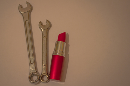 Red lipstick next to the wrenches. Independent decision-making, strength, leadership, strong character qualities. Vignetting, artificial lighting. 版權商用圖片