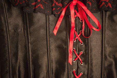 Red and black lace on a satin corset. Cross-lacing with scarlet ribbon and bow. Promise of pleasure, bed games.
