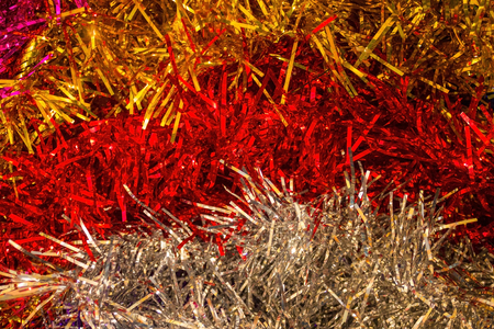 Brilliant, fluffy tinsel of different colors. Preparing for the holiday, decorating the house. Artificial lighting.