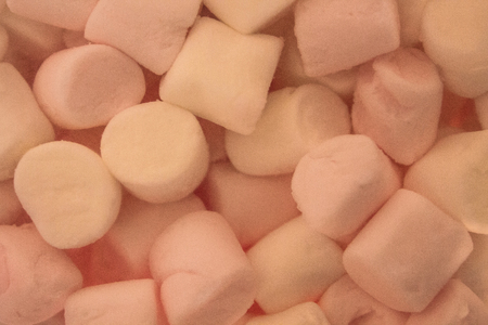 Light, white and pink pieces of tender marshmallows. Dessert, favorite baby treat. View from above.
