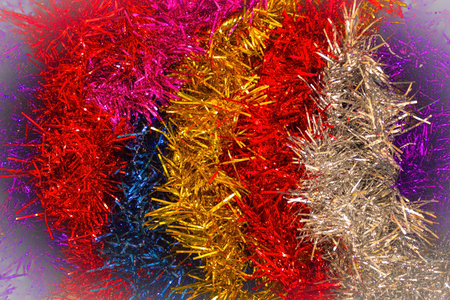 Celebratory background of shiny tinsel. Red, blue, gold and silver colors. Decoration for the Christmas tree and for the premises. Merry children's party, carnival. Vignetting. Archivio Fotografico