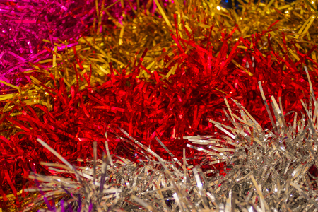Bright stripes of shiny tinsel. New Years, festive background. Macro photography, artificial lighting.