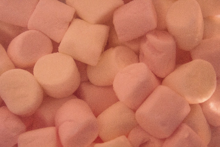 Delicate air dessert. White and pink slices of tender marshmallows, baby delicacy. Macro photography, artificial lighting, the background is blurred. Фото со стока