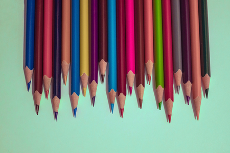 A number of bright, sharply sharpened pencils of different colors. Brainstorming, task for creativity of thinking, teamwork. Light background, top view.